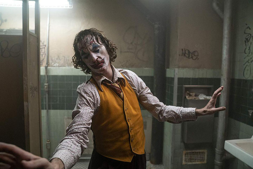 Joaquin Phoenix as Arthur Fleck dancing in a bathroom after his first murders.