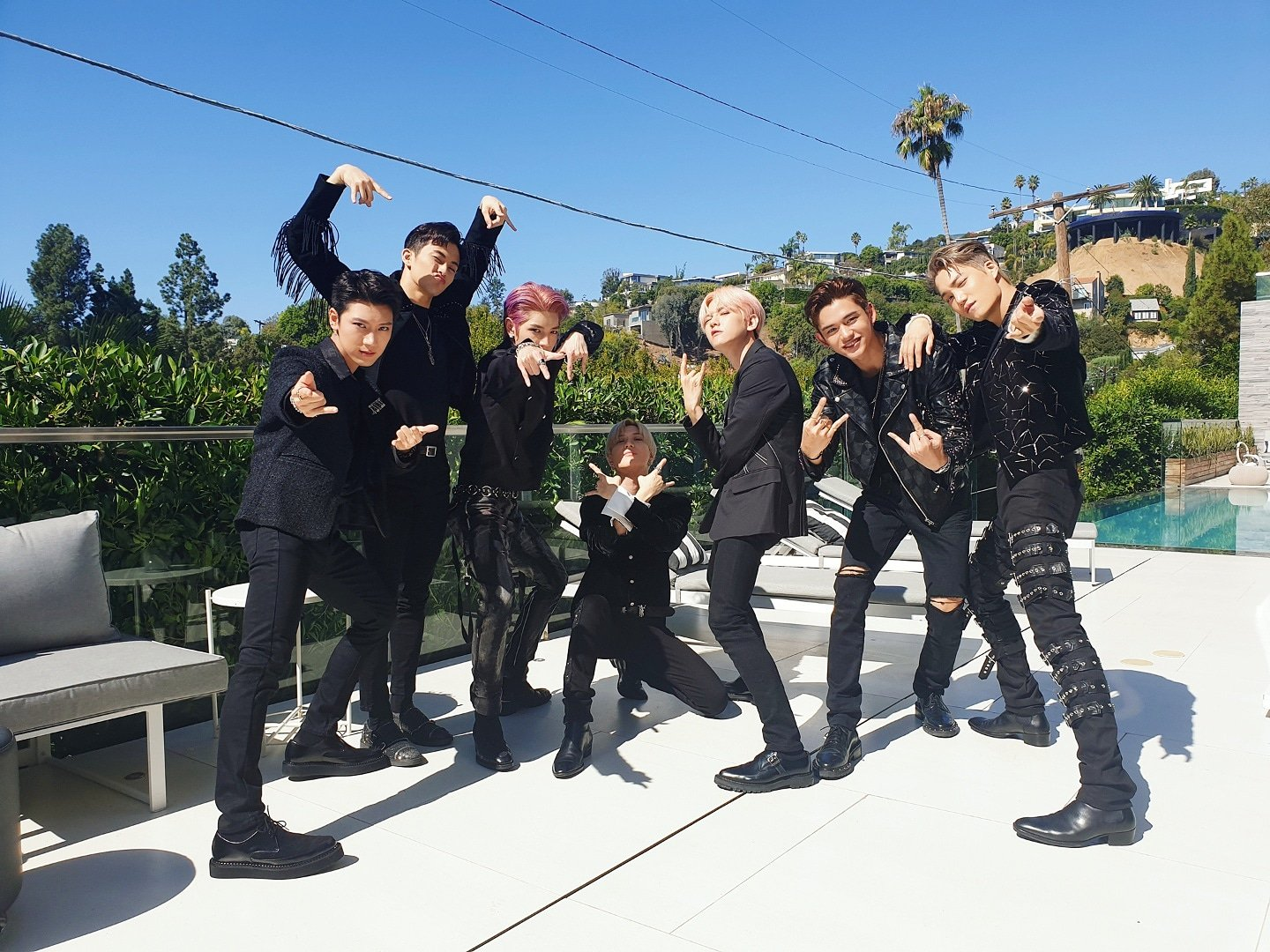 SuperM posing outdoors in their stage outfit, from left to right: Ten, Mark, Taeyong, Taemin, Baekhyun, Lucas, Kai.