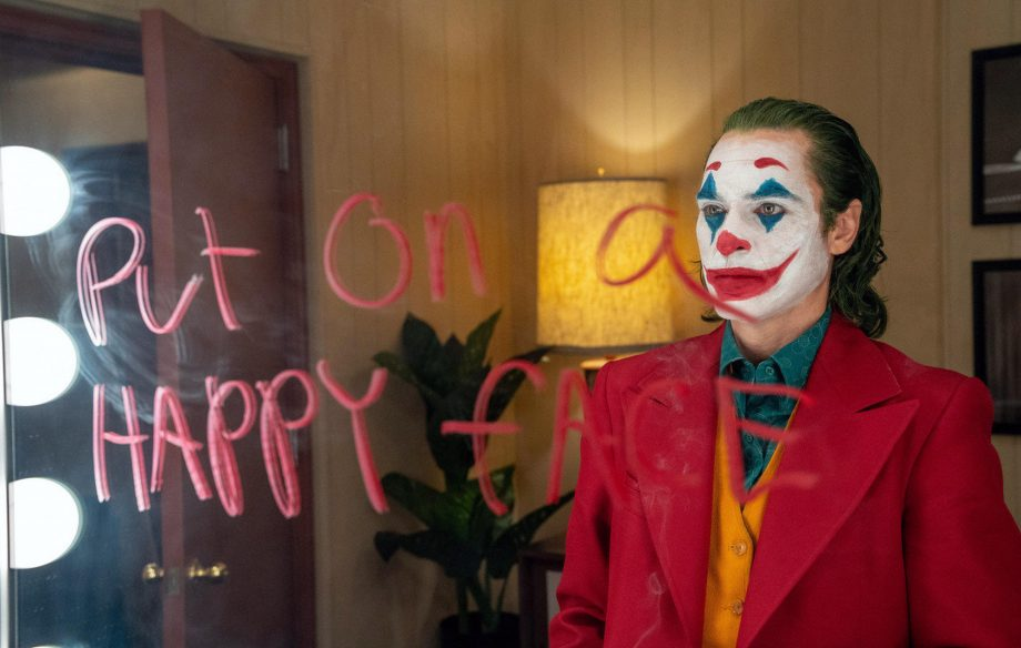 "Joker stares into mirror with ""put on a happy face"" written across it. He's gearing up to go on the Murray show."