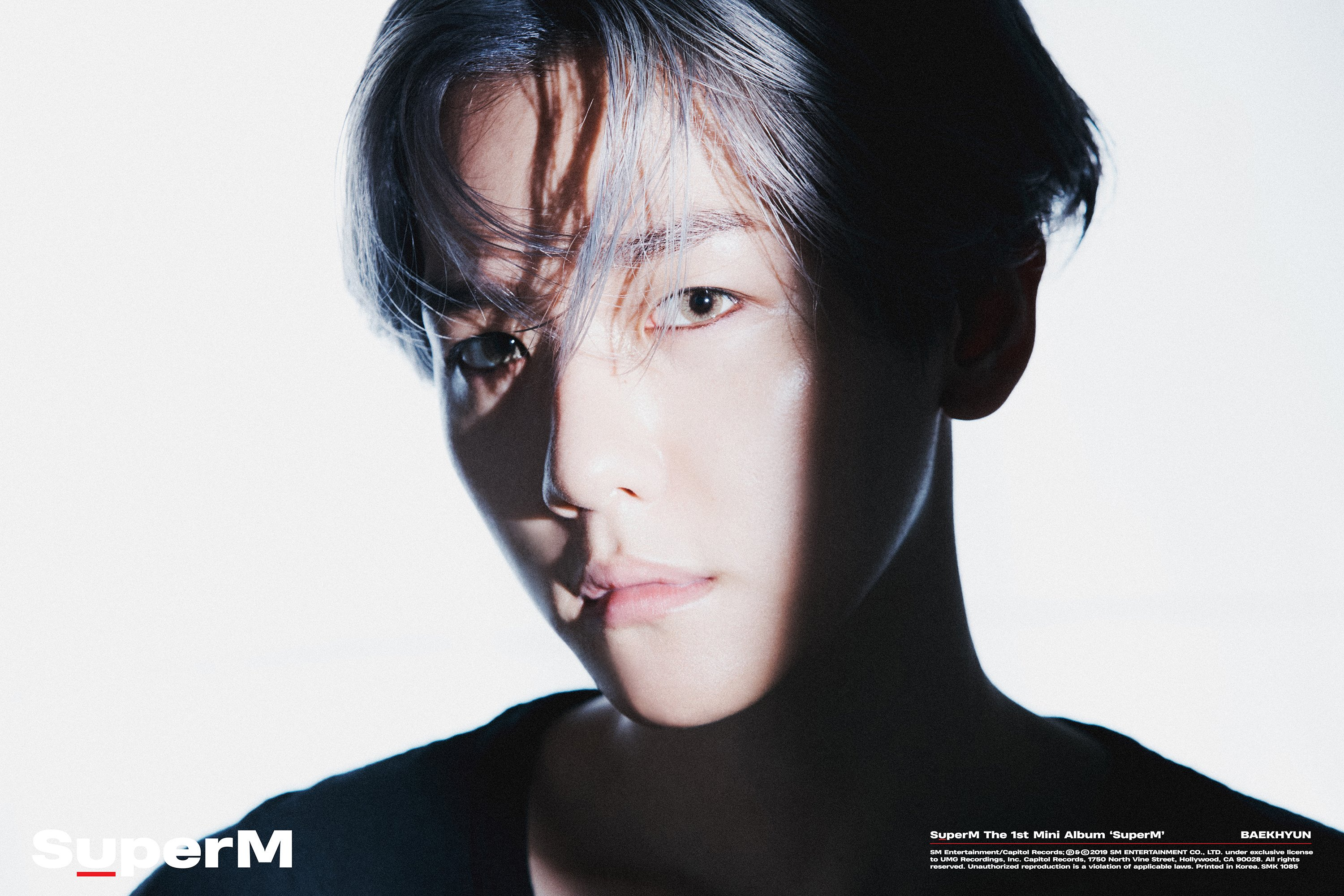A portrait shot of Baekhyun, SuperM's leader, with his face only partially lit.