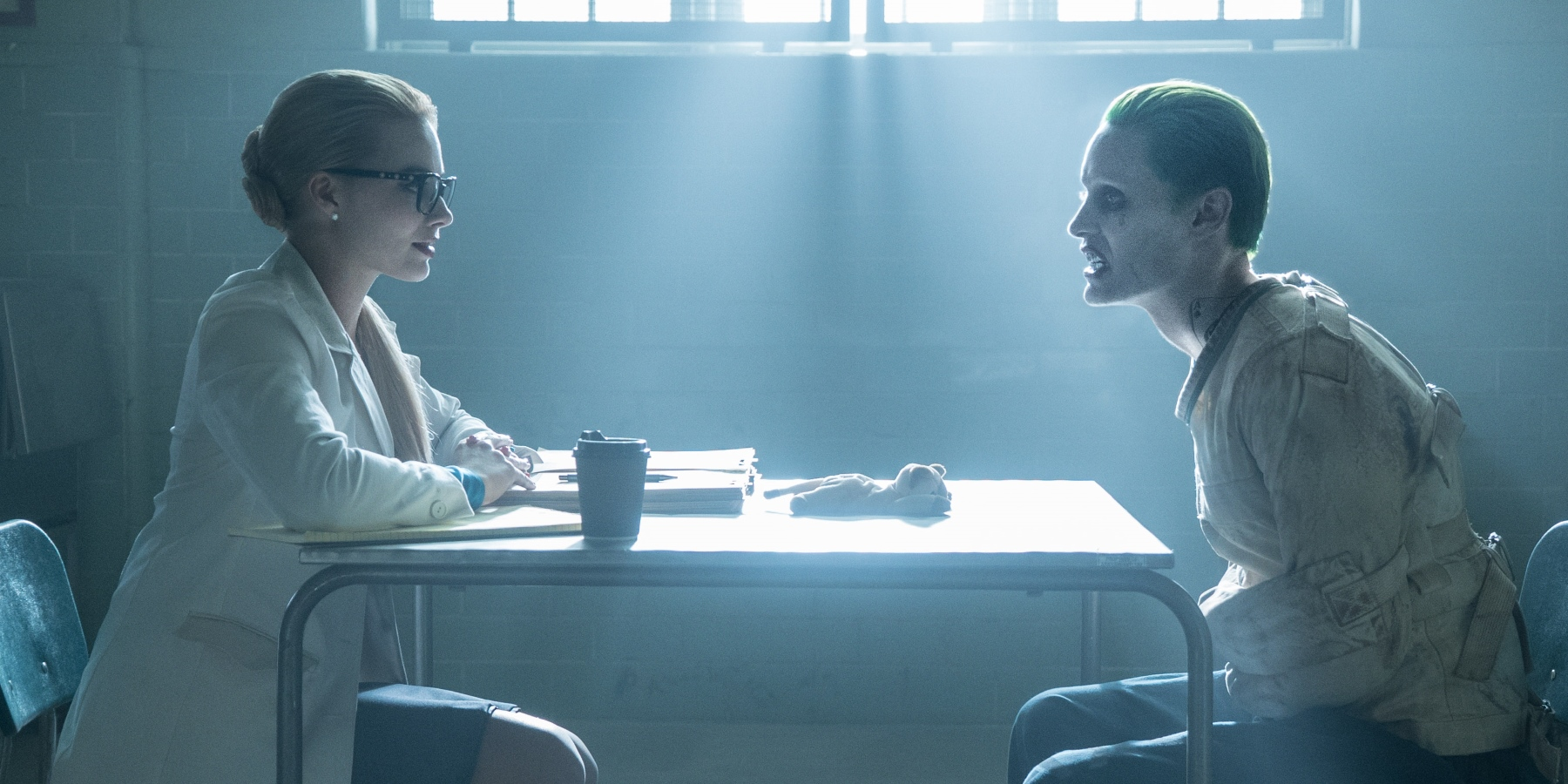 Harleen Quinzel and the Joker sit across from each other at a table.