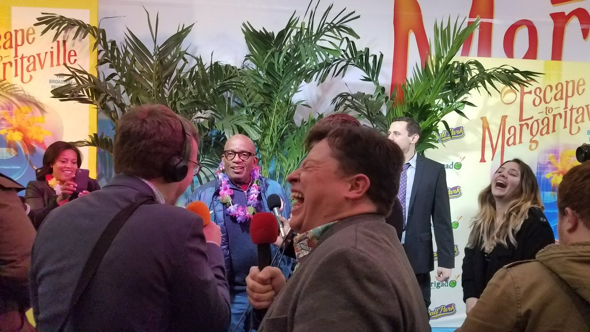 Justin and Griffin laughing as Al Roker mocks their clunky equipment at the premiere of Escape to Margaritaville.