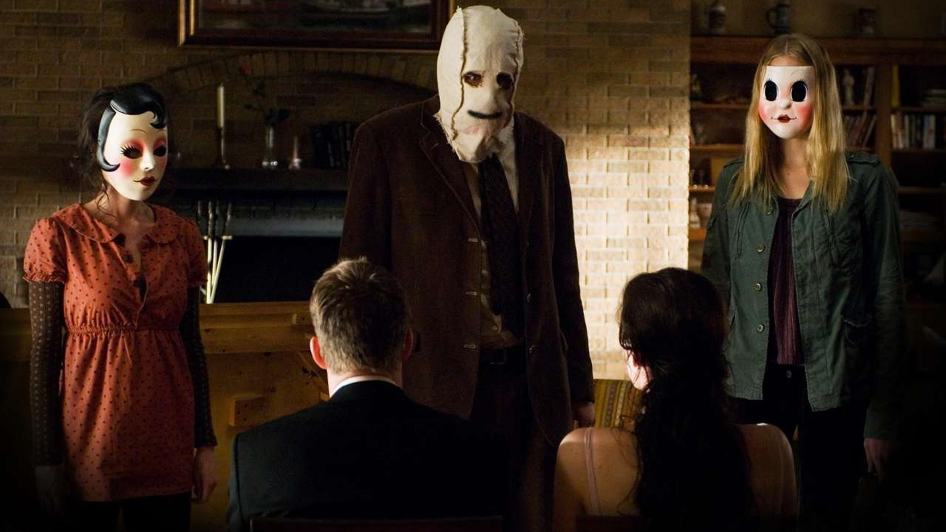 Three killers from the strangers standing in front of the two victims of the movie