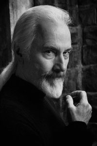 Rick Baker, now 68 years old. He stares into the camera and has his iconic long, white hair pulled into a  pony tail.