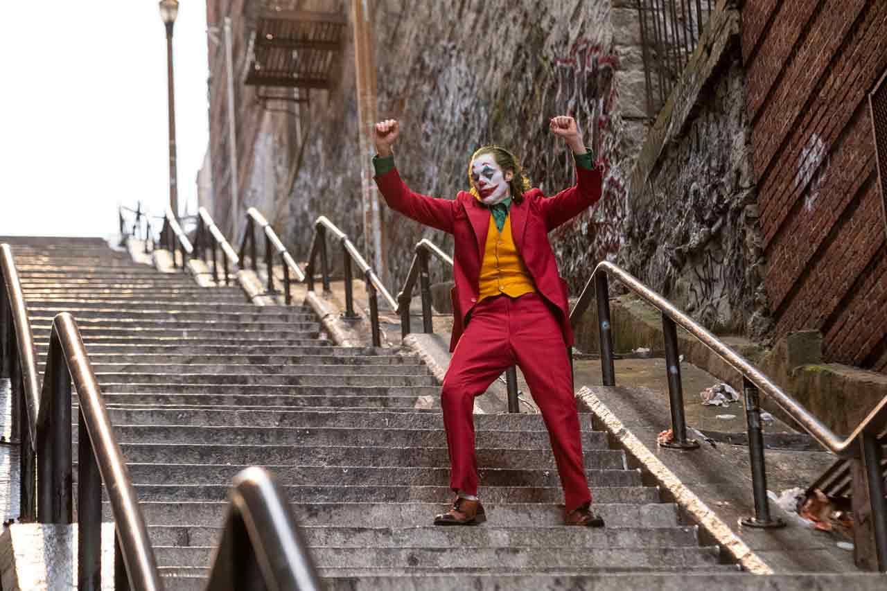 Joaquin Phoenix as the Joker dancing down a set of stairs excited about his new found confidence.
