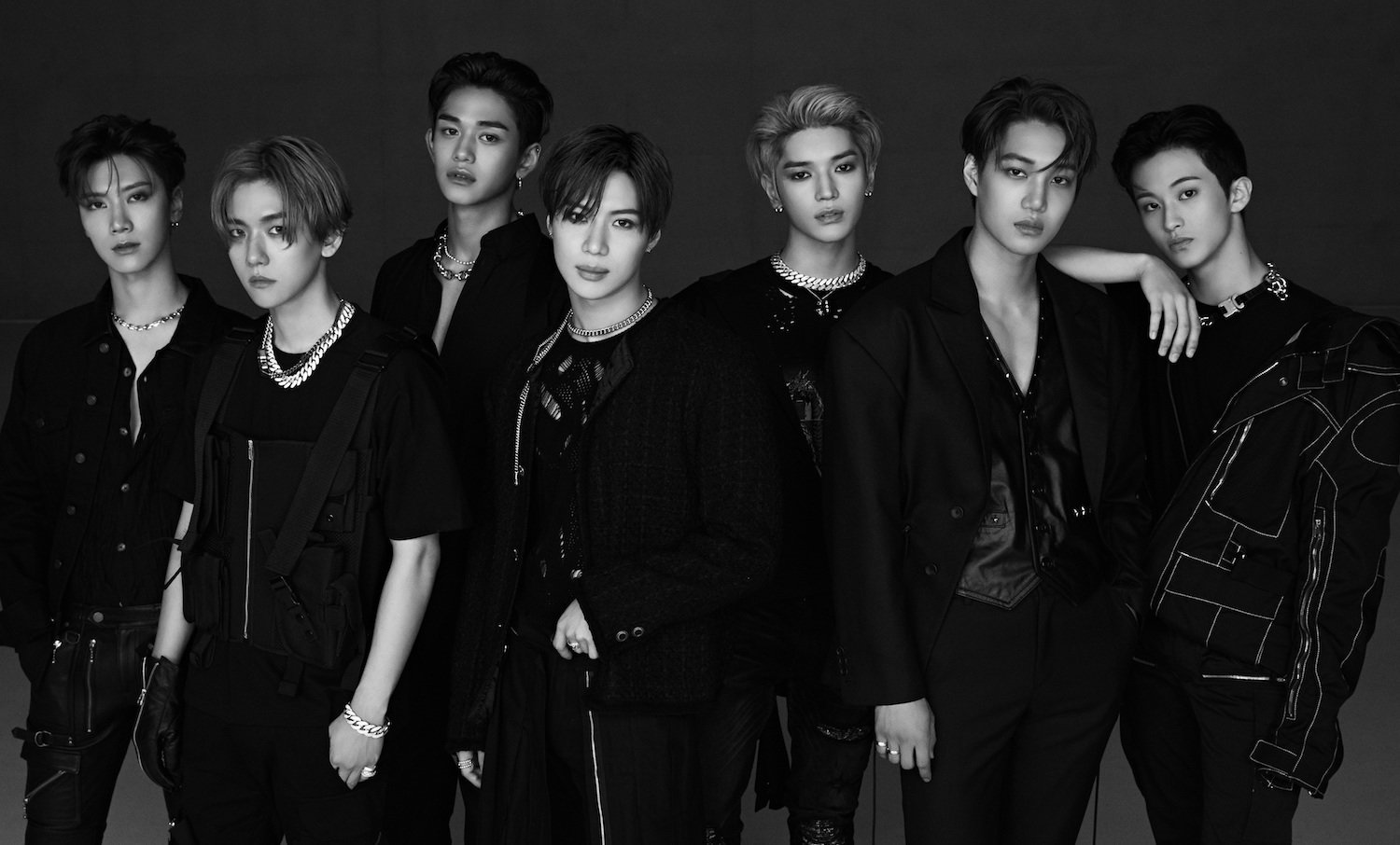 SuperM are lined up, from left to right: Ten, Baekhyun, Lucas, Taemin, Taeyong, Kai, Mark.