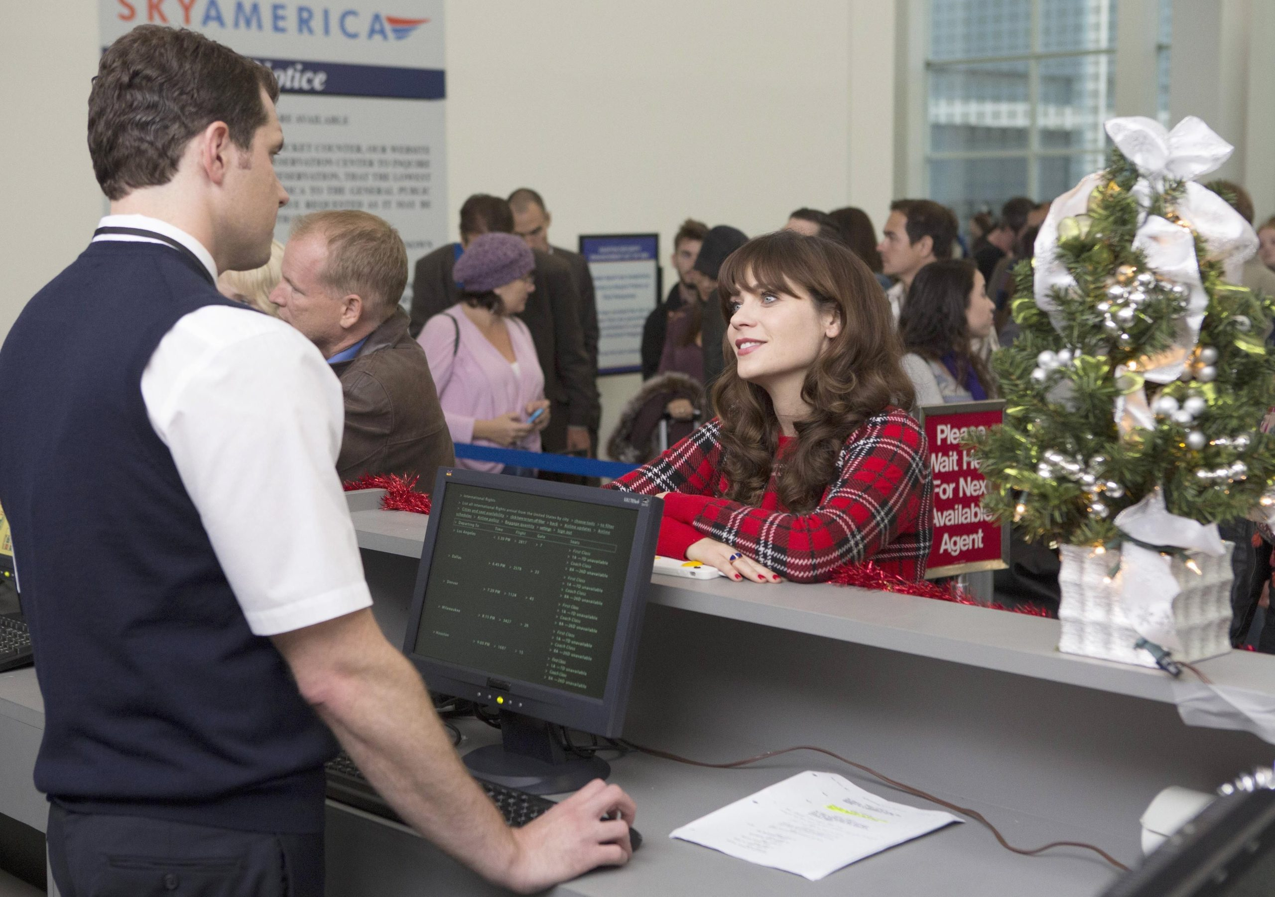 In sitcom New Girl, Jess stands at the ticket counter in the airport, talking to an employee.
