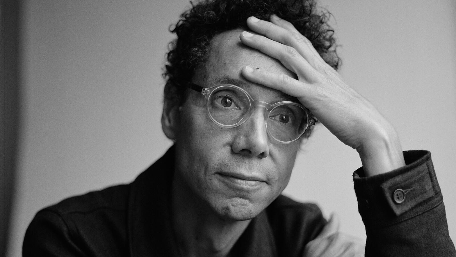 Gladwell looking into distance with hand rested on forehead.