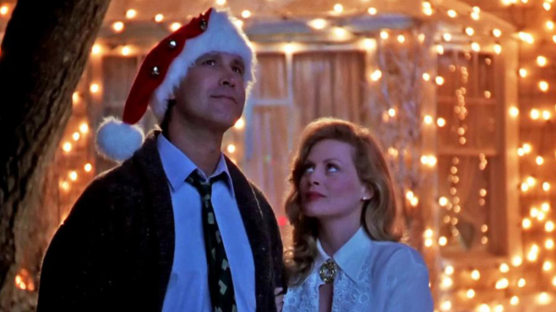 Ellen looking up at Clark as the Griswold house behind them shines brightly from lights for the holidays.