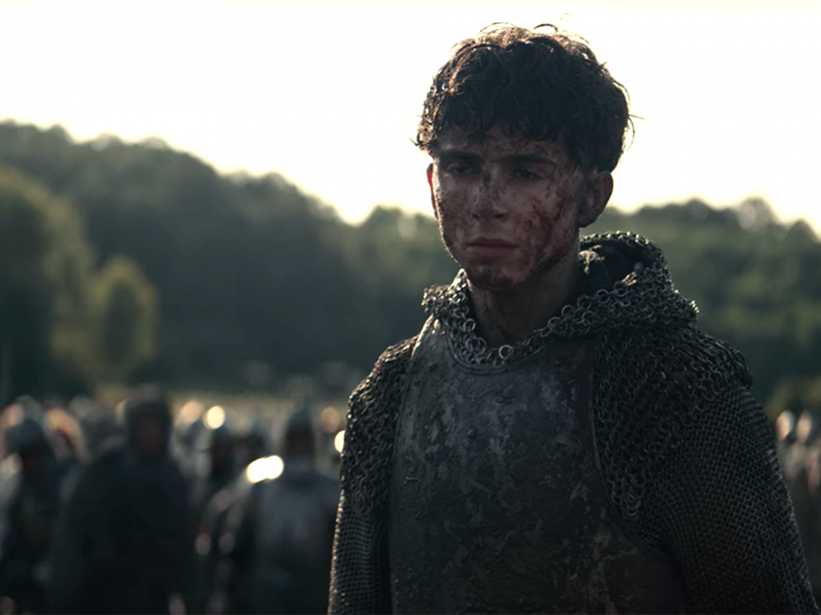King Henry V stands muddied in front of his troops after battle.