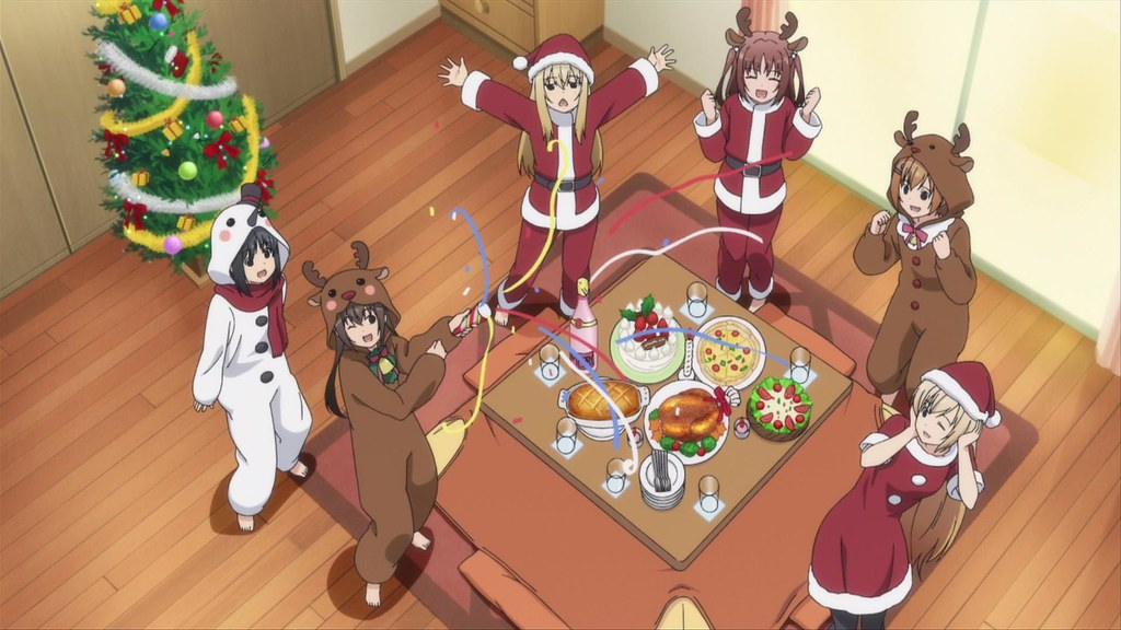 Three girls in santa suits, two girls in reindeer suits, and one girl in a snowman suit standing around a Christmas feast