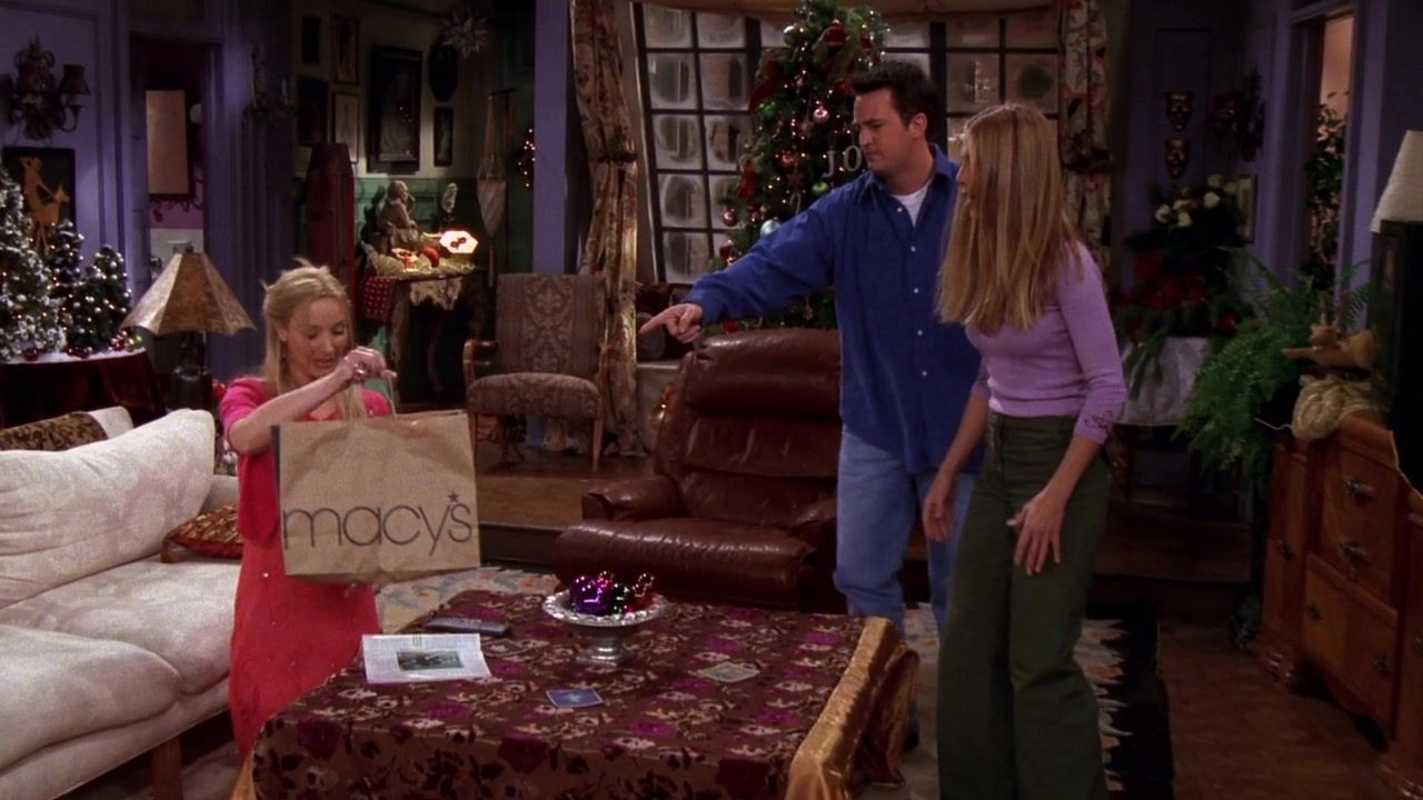 Phoebe holds a Macy's bag and Chandler points at her, with Rachel standing next to him.
