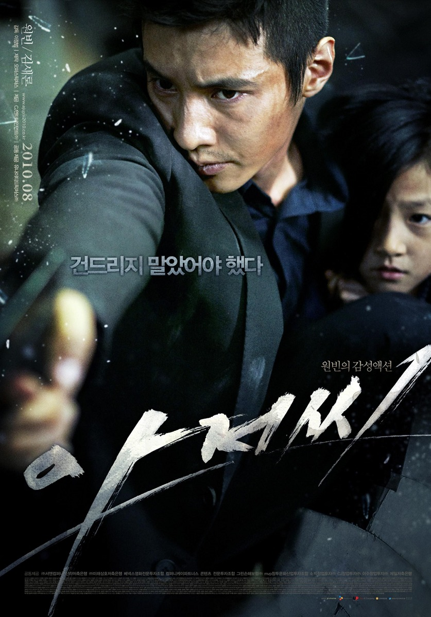"""In the Korean film cover of """"The Man From Nowhere,"""" Cha Tae Sik holds Jung So Mi close as he aims a pistol."""