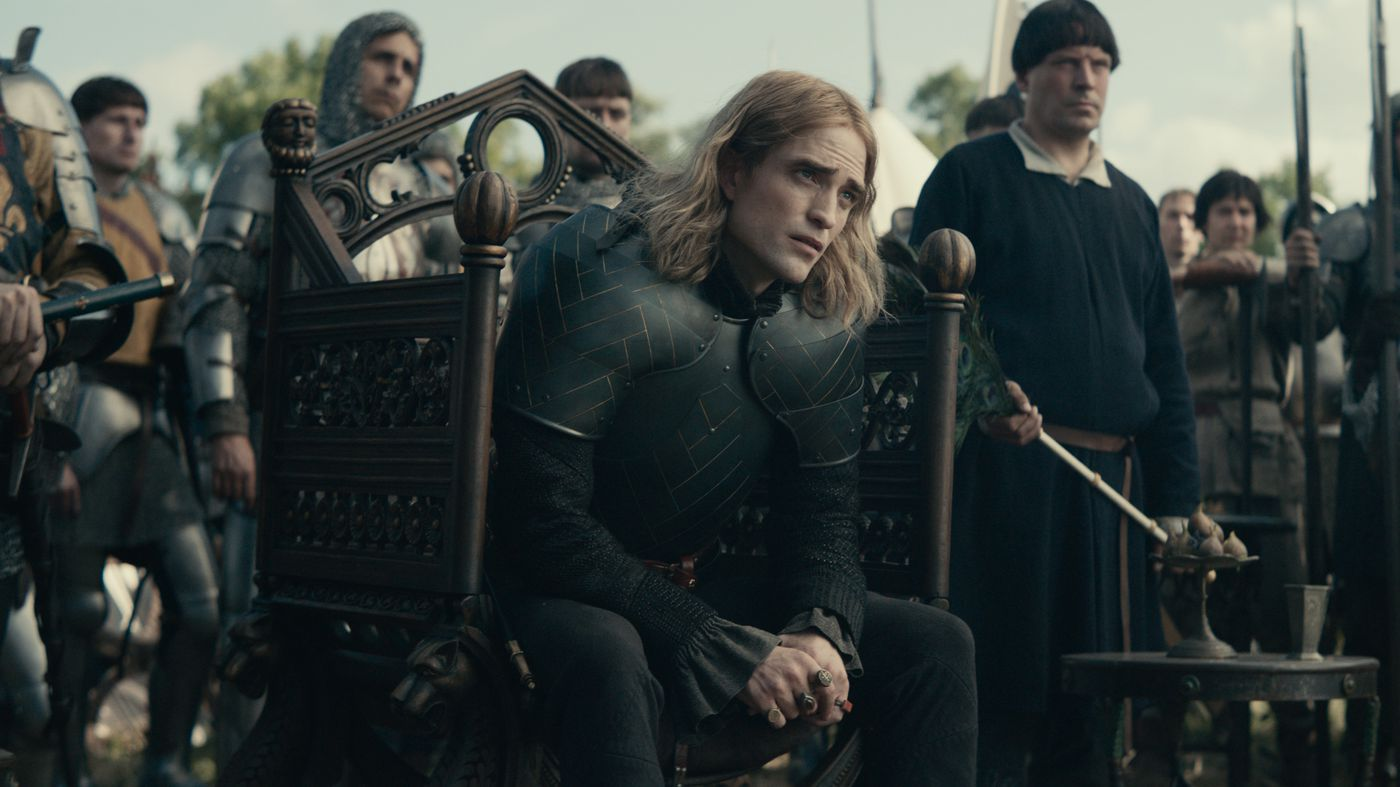 Robert Pattinson as The Dauphin sits on a throne in front of his army.