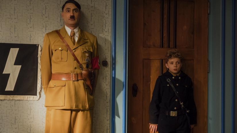 Jojo (Roman Griffin Davis) and Adolph Hitler (Taika Waititi) have their backs against a wall.