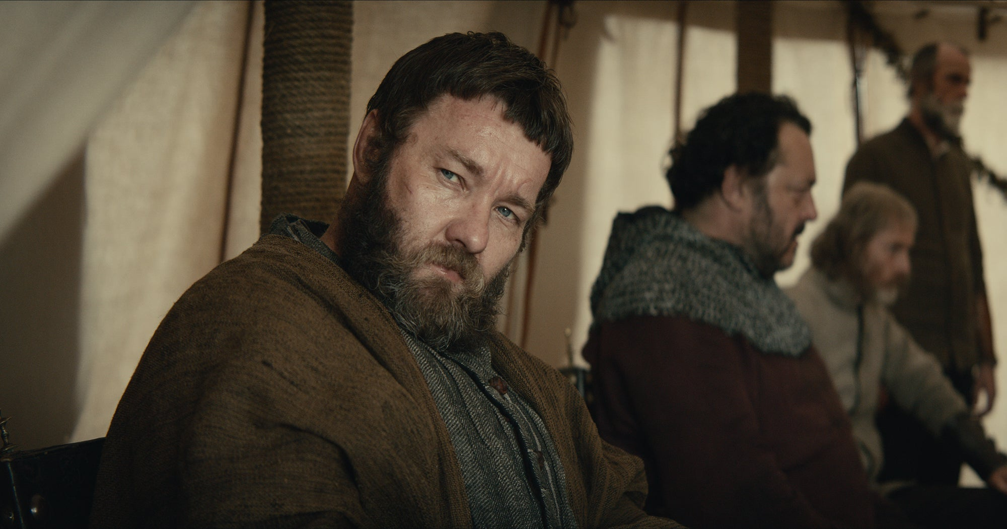 Sir John Falstaff sits in a tent among other advisers to the King.