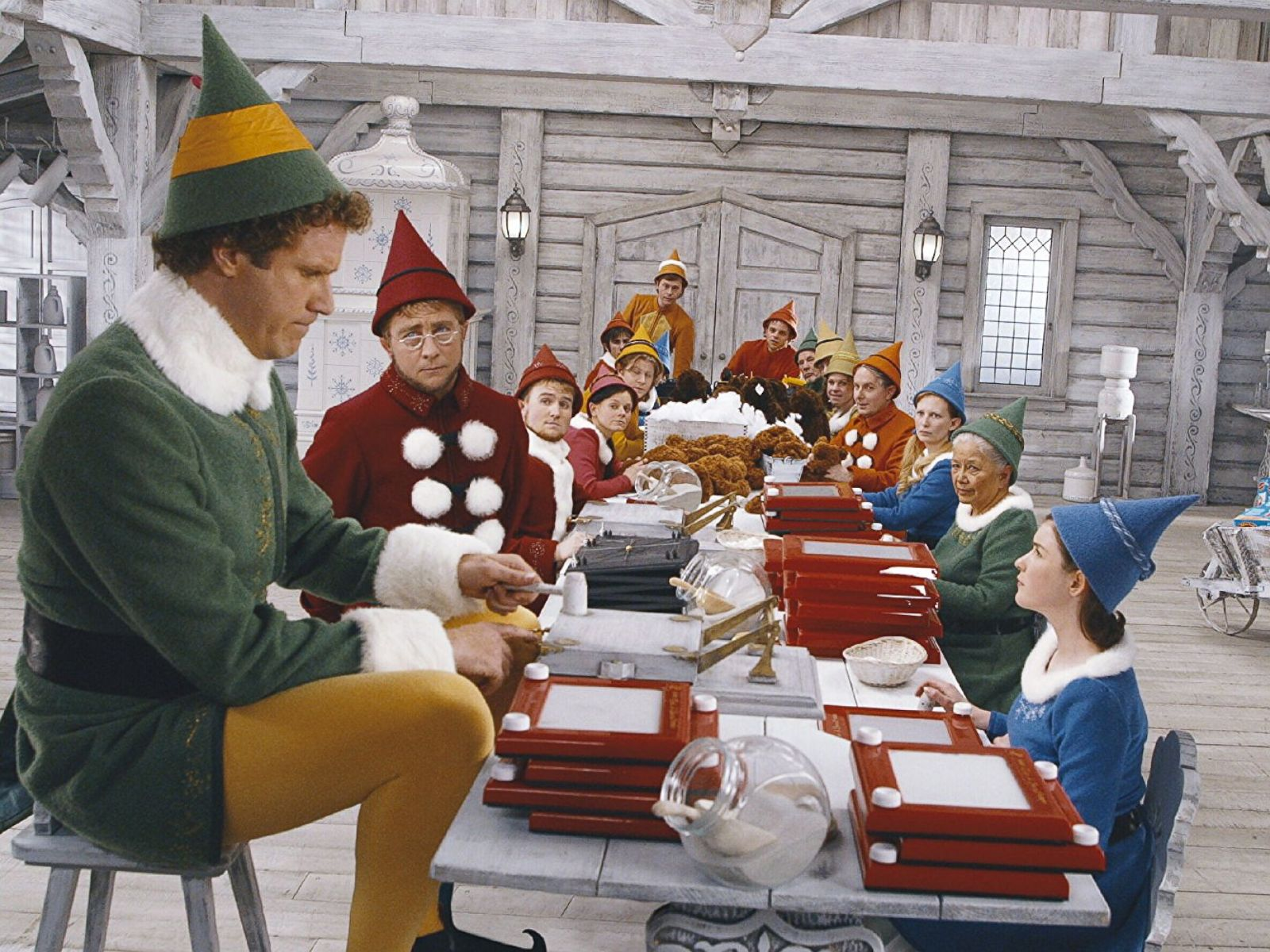 Buddy the elf sitting with all the other elves, very obviously bigger than the others.  They are working on toys for the holiday season.