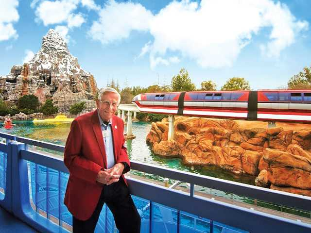 Imagineer Bob Gurr standing by the monorail and the Matterhorn, two vehicles he designed for the park.
