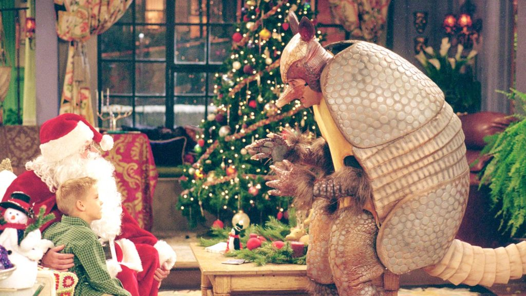 Ross wears an armadillo costume and talks to Ben and Santa who sit on the couch.