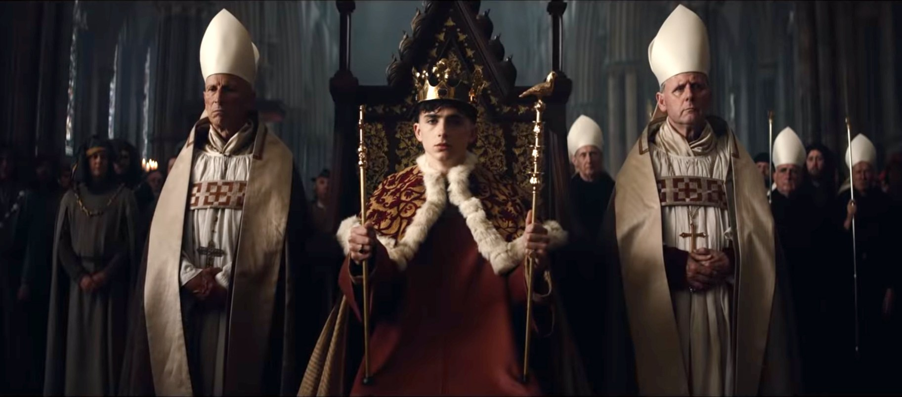 Timothee Chalamet as King Henry V, sits on a throne in robes and holding a scepter.