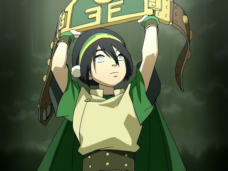 Toph, as the Blind Bandit, holds up her championship belt.