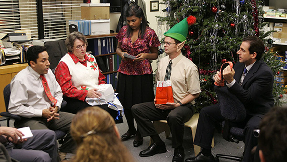 Michael, Dwight, Kelly, Phyllis, and Oscar sit in a circle at a Christmas Party in sitcom, The Office.