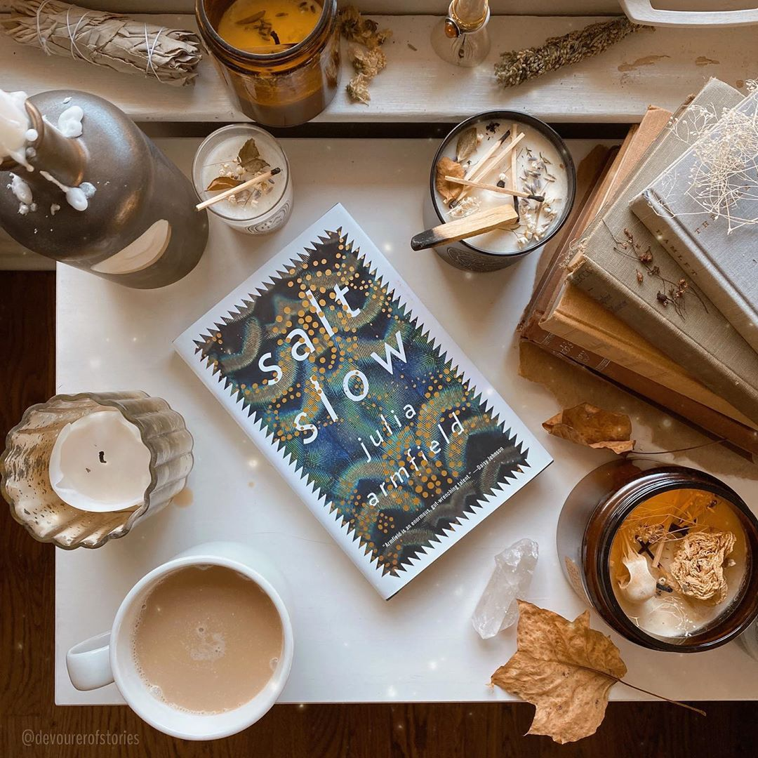 A book flat lay featuring Salt Slow surrounded by coffee, candles, and leaves.