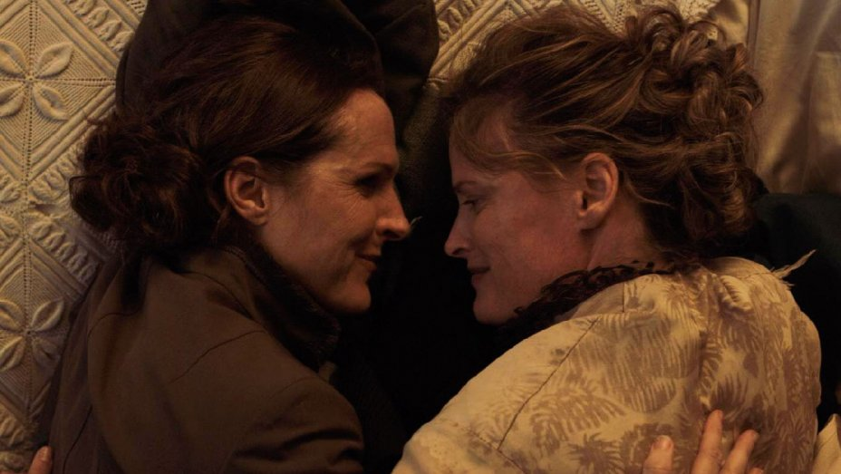 Still from WILD NIGHTS WITH EMILY featuring Emily (Molly Shannon) and Susan (Susan Ziegler) looking lovingly at each other while lying in bed.