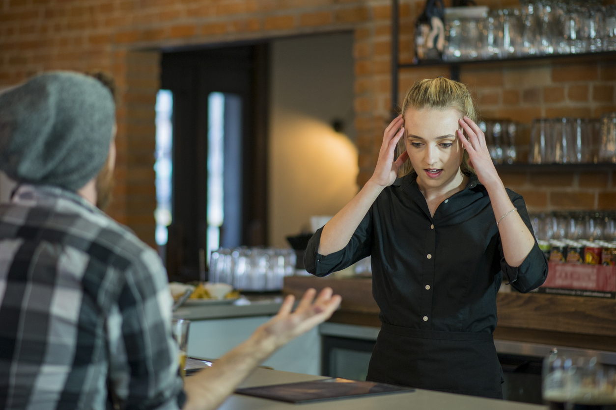 Stressed female young adult waitress holding her head in stress as customers complain to her behind the bar of a restaurant.