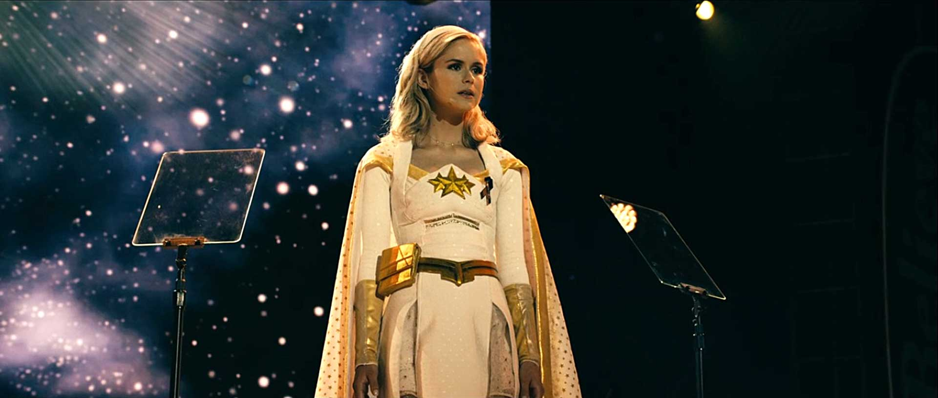 Annie January, also known as Starlight, stands upon a stage with a night sky backdrop, looking out into the distance.