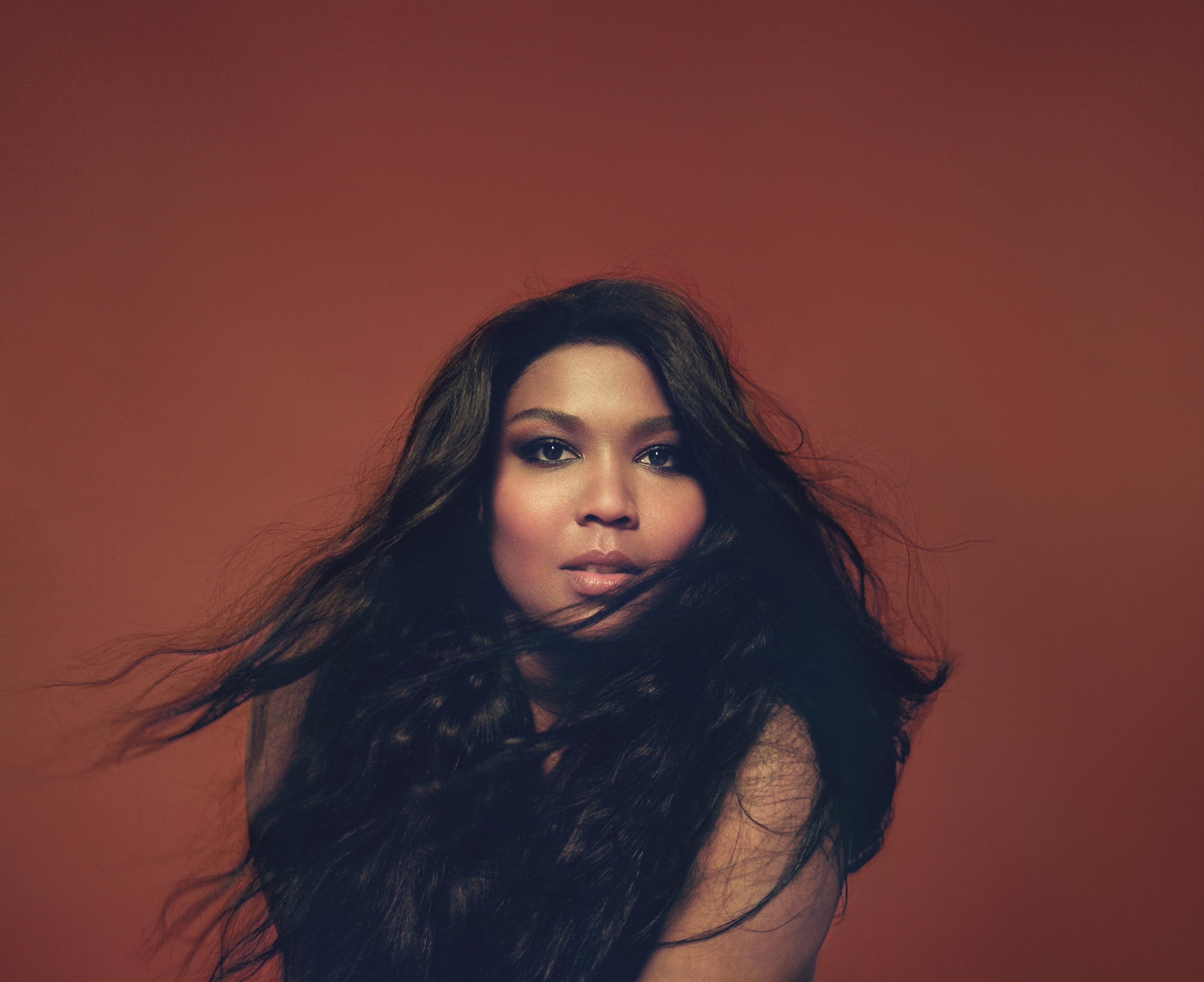 Lizzo posing in front of a brown backdrop