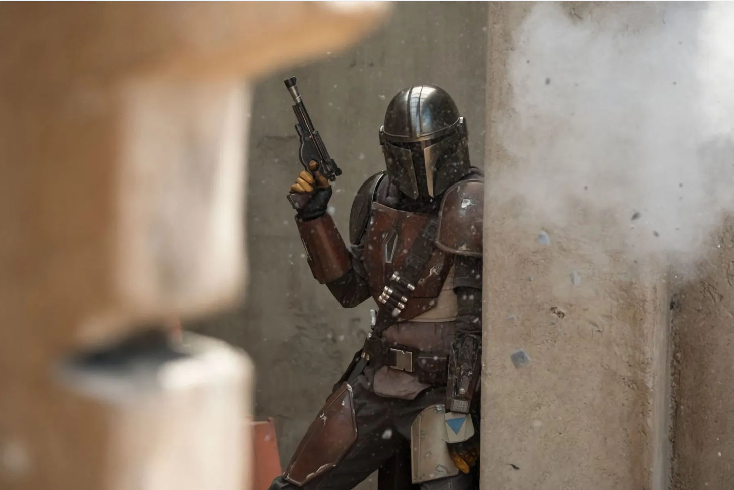 The Mandalorian mid-shoot off leaning behind a wall with pistol in hand.