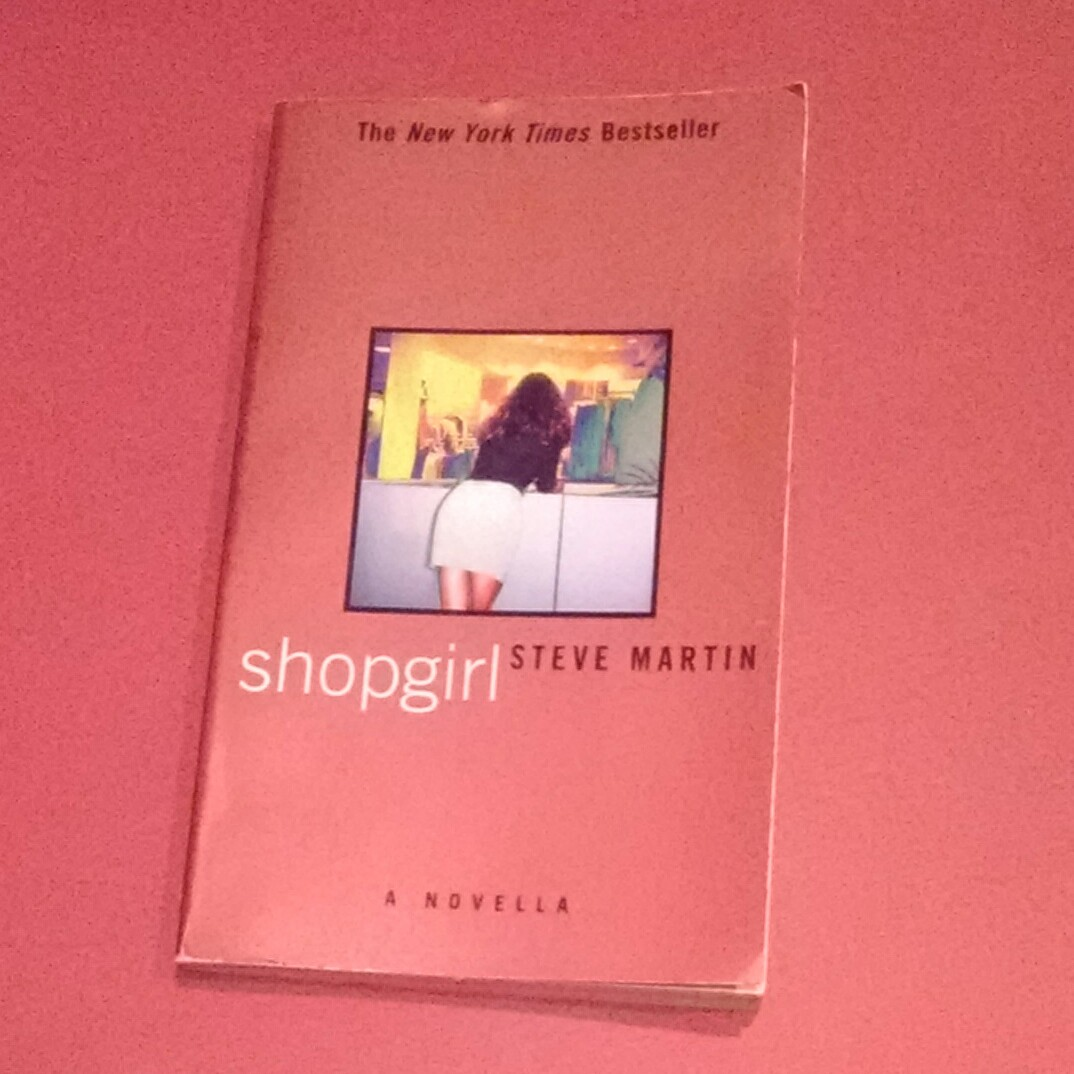 Martin's book, Shopgirl, laying on a red backdrop.