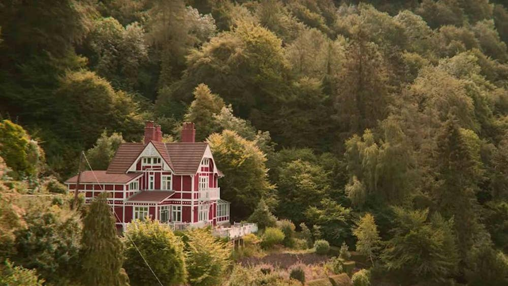 A wide shot of Otis' large, red house on rolling, green hills.