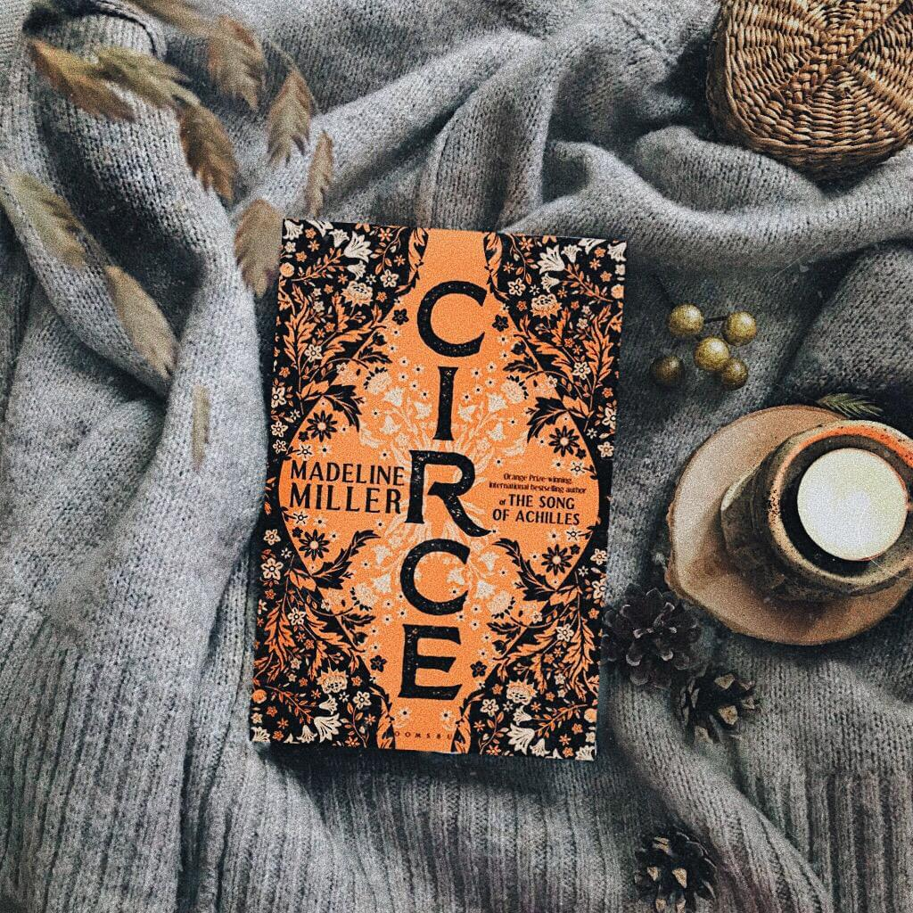 Quarter-Life Crisis Books: Madeline Miller's book to read, Circe, laying on a sweater surrounded by wood, leaves, and a basket.