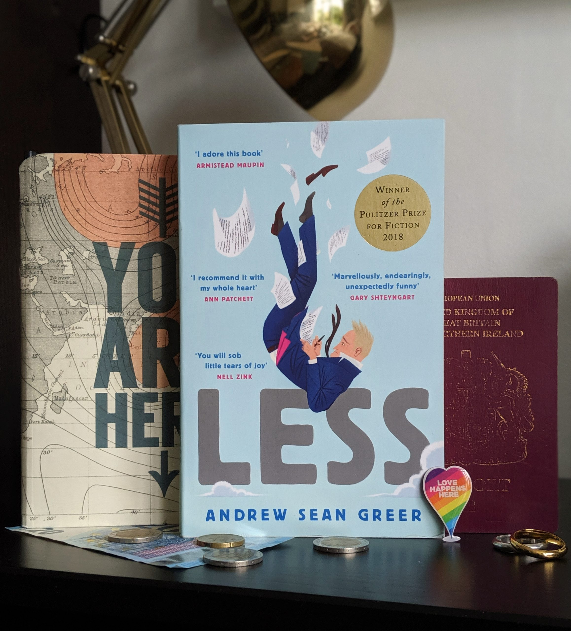 Quarter-Life Crisis Books: Andrew Sean Greer's book, Less, sitting in front of a map and passport.