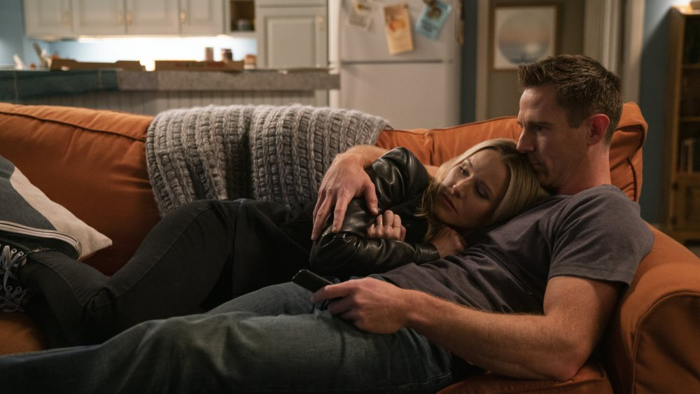 Logan and the main heroine cuddled up on a couch.