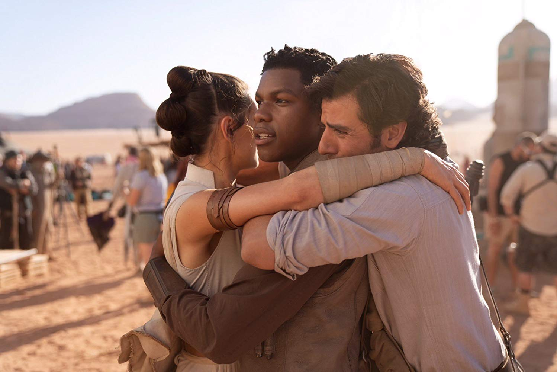 Behind the scenes photo of Daisy Ridley (Rey) hugging John Boyega (Finn) and Oscar Isaac (Poe)