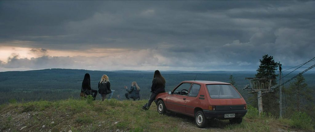 Heavy Trip's band with their backs to the camera as they sit with their parked car.  They are on a hill overlooking a wide, natural landscape.