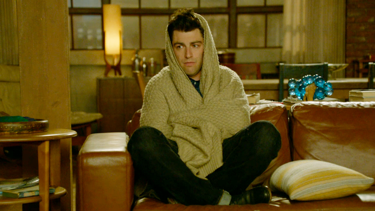 Schmidt from New Girls curled up on a couch.