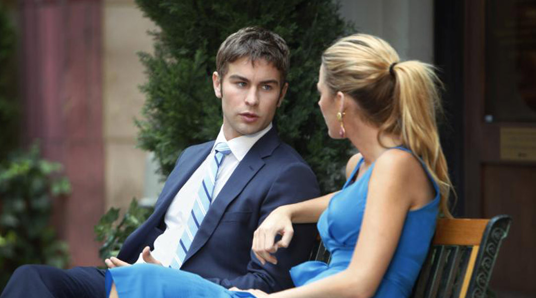 Nate and Serena sit together on bench, both dressed in blue.
