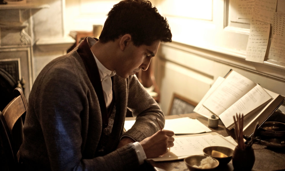 Ramanujan from The Man Who Knew Infinity sits at desk writing down new mathematical ideas.