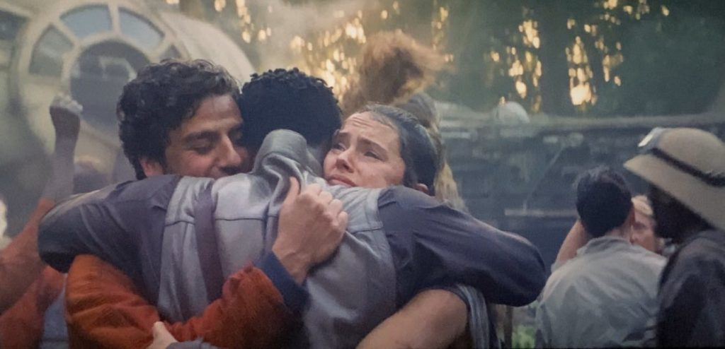 Poe Dameron, Finn, and Rey hug after reuniting following the battle of Exegol