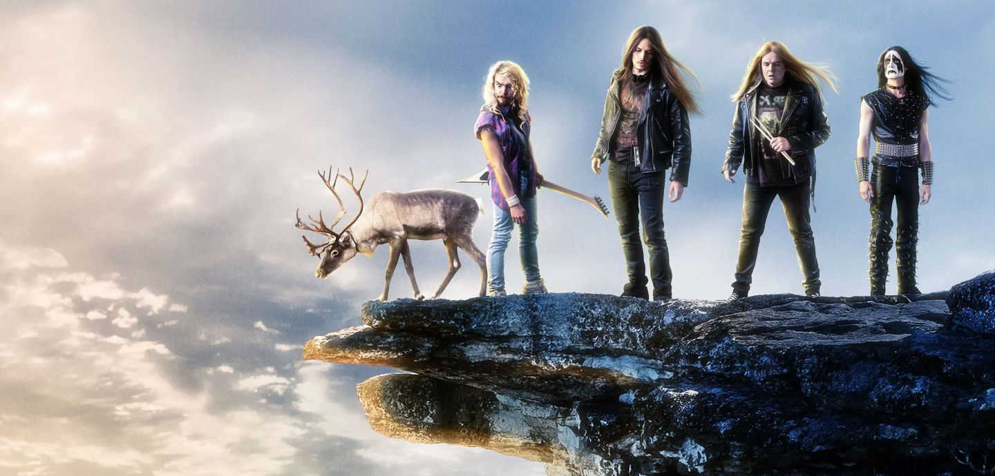 The death metal band lined up on a cliff with a reindeer.