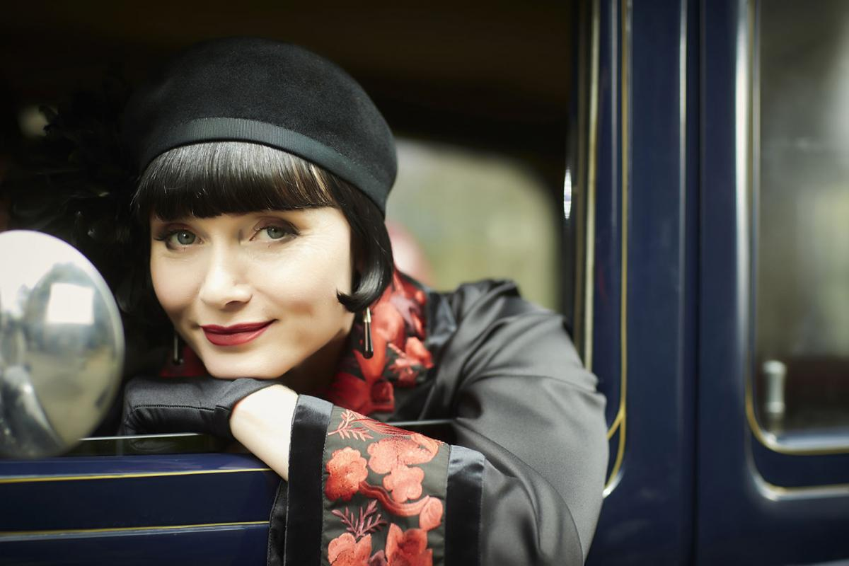 Phryne Fisher leaning out of a car window.