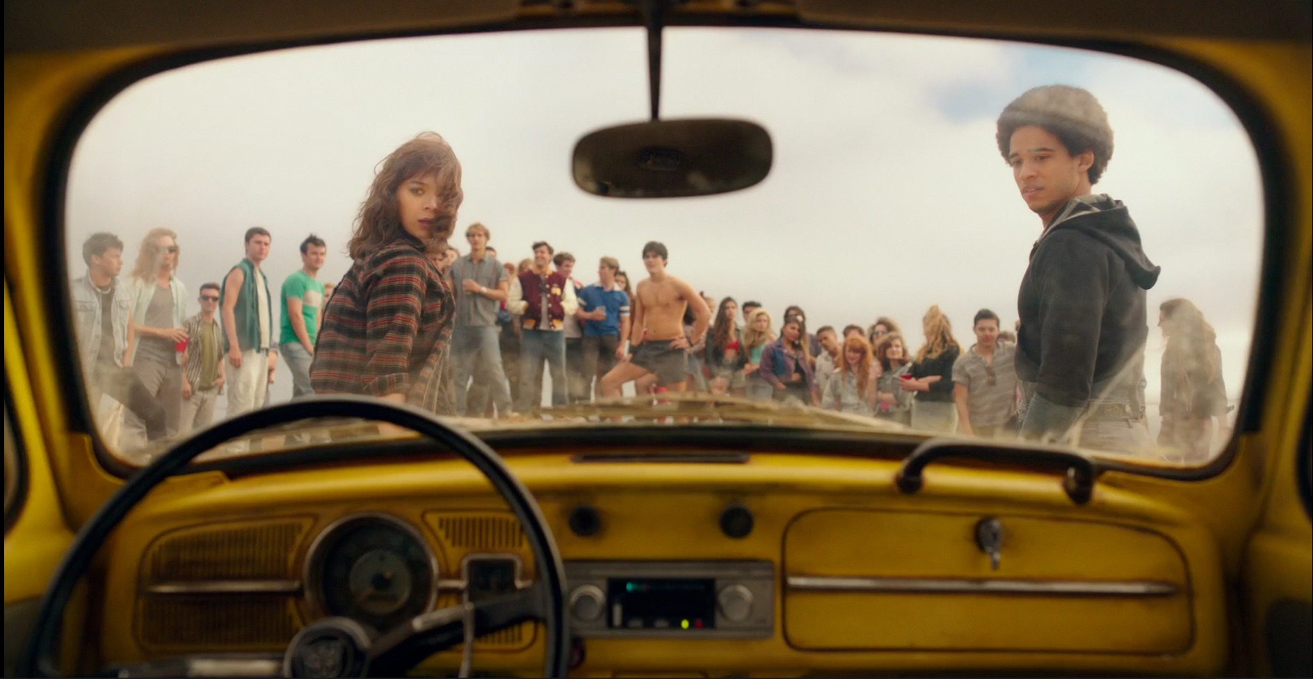 Charlie, Memo, and a group of teenagers, viewed through the windshield of Bee's car-mode.