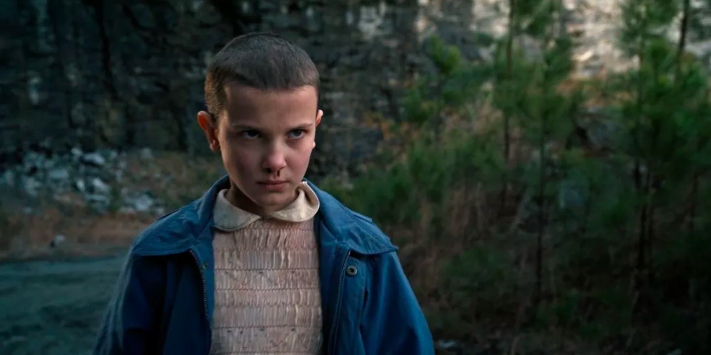 Keep You Entertained: Eleven staring into the distance with a bloody nose and her season one shaved head in season one of the entertaining Stranger Things Series.