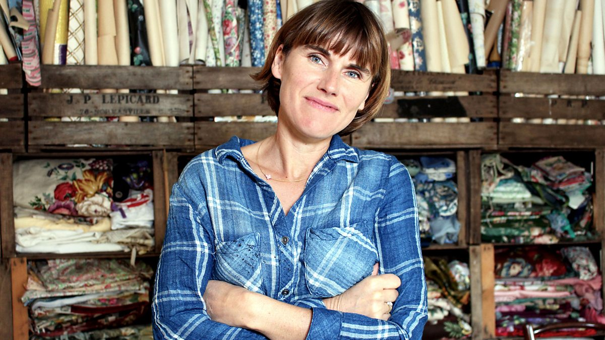 Sarah More standing in front of a wall of fabrics.