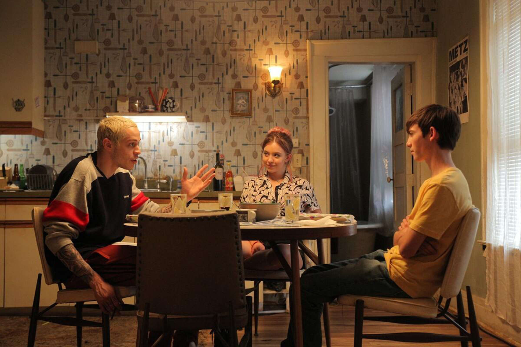 Zeke (Davidson), Holly (Sweeney), and Monroe (Gluck) have a chat during a feel-good dinner.