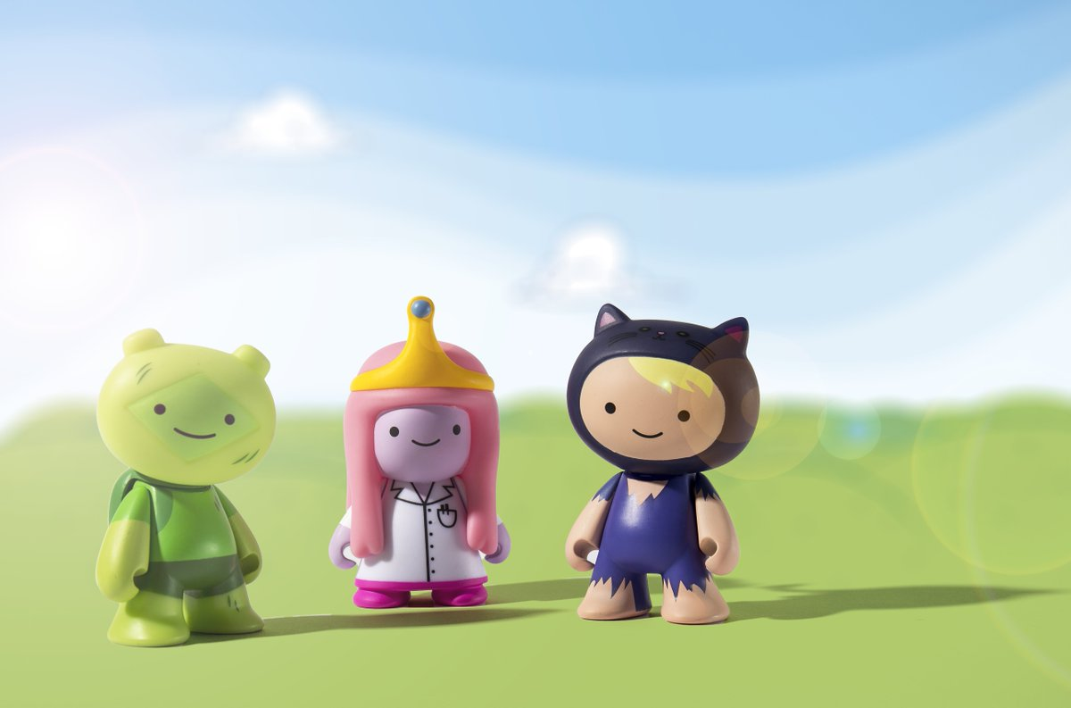 Figures of Adventure Time characters posed against a sunny, grassy field background.